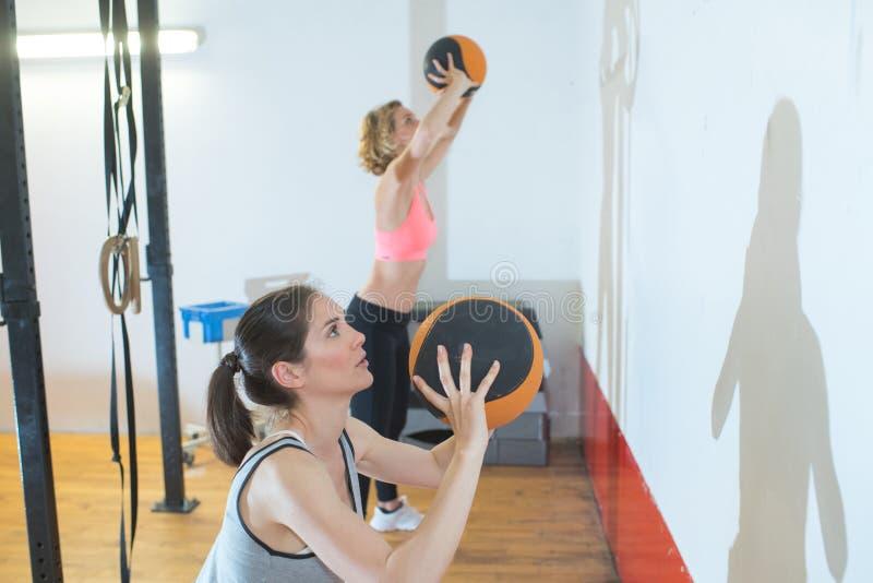 Kvinnor som kastar medicinbollen upp mot väggen arkivfoton