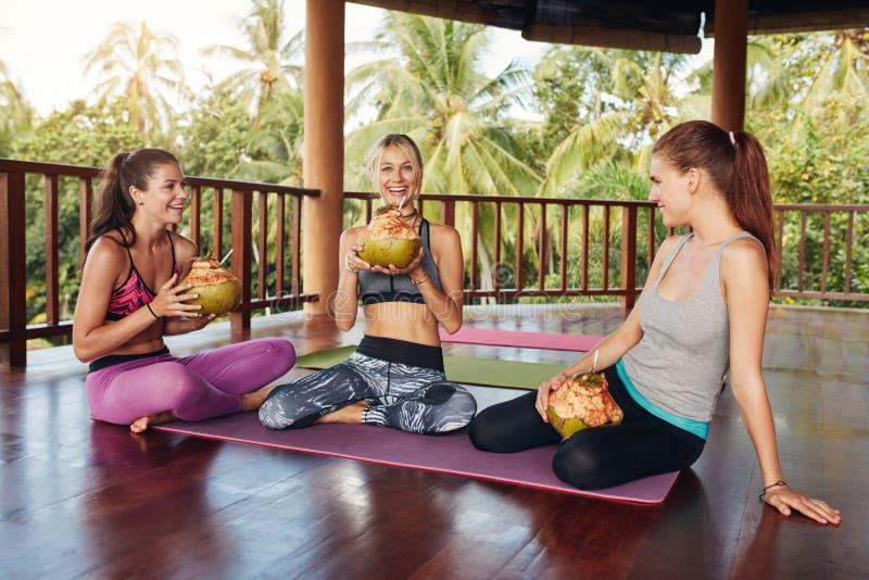 Kvinnor som kopplar av med kokosnötfruktsaft efter yogagrupp royaltyfri bild