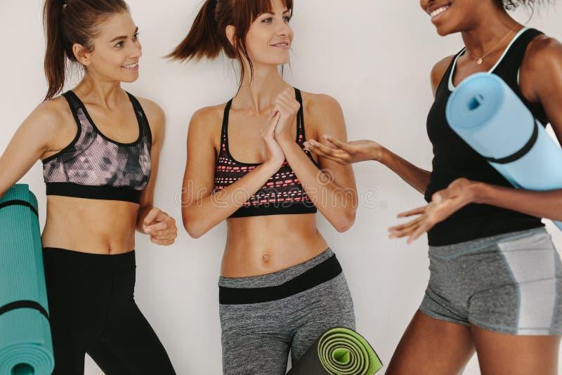 Kvinnor som kopplar av och talar efter yogagrupp arkivfoton