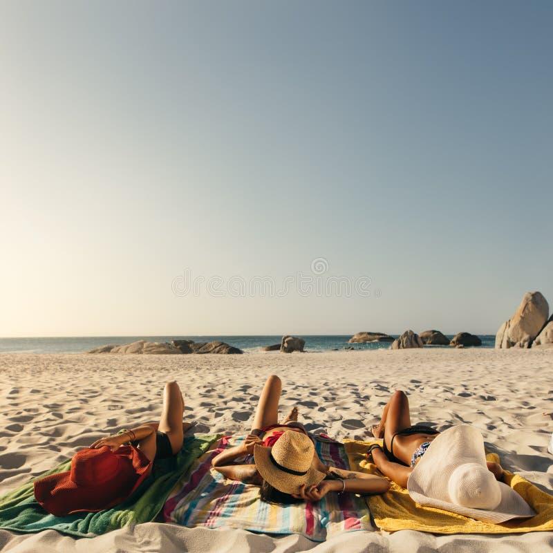 Kvinnor som kopplar av på de bärande solhattarna för strand royaltyfria foton