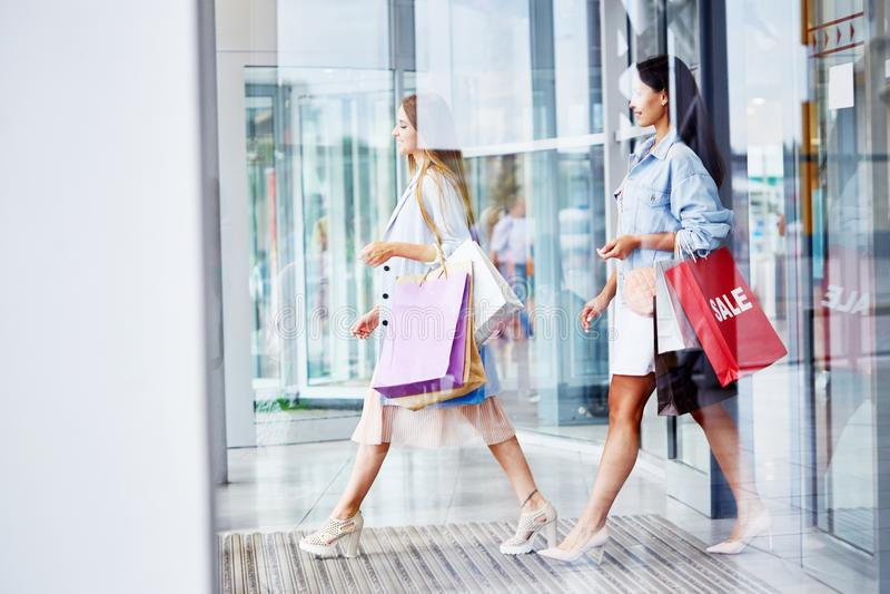 Kvinnor som lämnar köpcentret med pappers- påsar royaltyfri bild