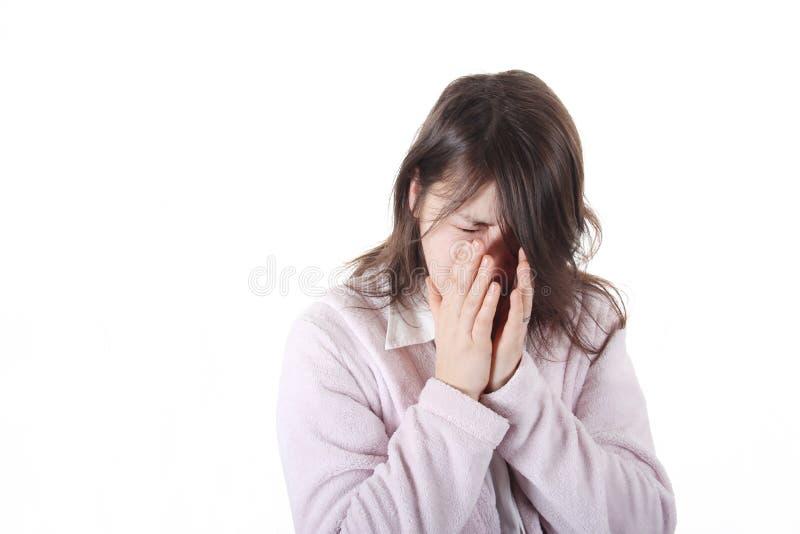 Kvinnor som nyser i hennes händer royaltyfria foton