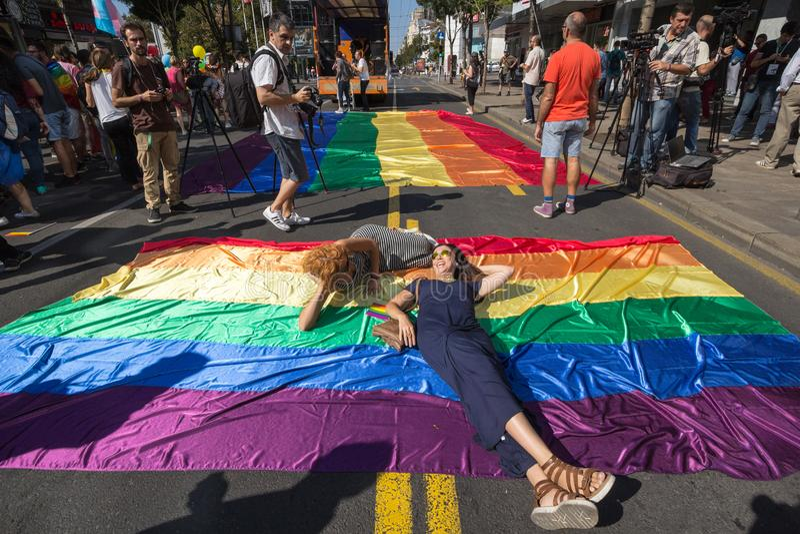 Kvinnor som poserar att lägga på en glad flagga för enorm regnbåge under Belgrade den glade stoltheten Ståta hände i år utan prob royaltyfri fotografi