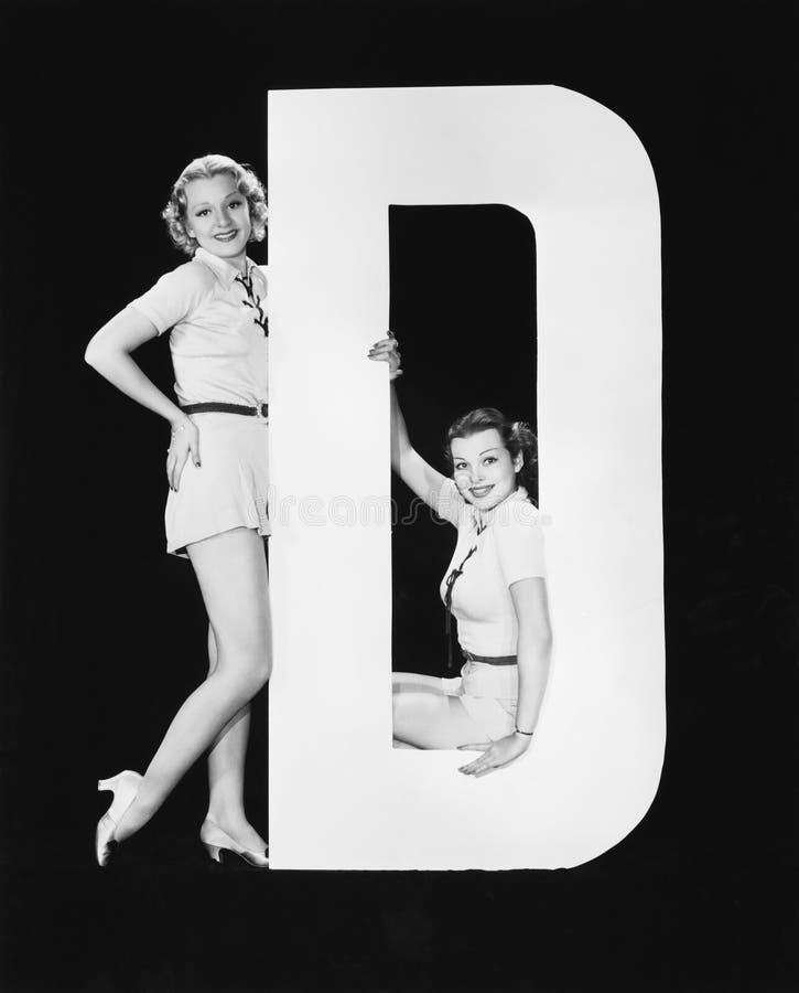 Kvinnor som poserar med enorm bokstav D (alla visade personer inte är längre uppehälle, och inget gods finns Leverantörgarantier  royaltyfri bild