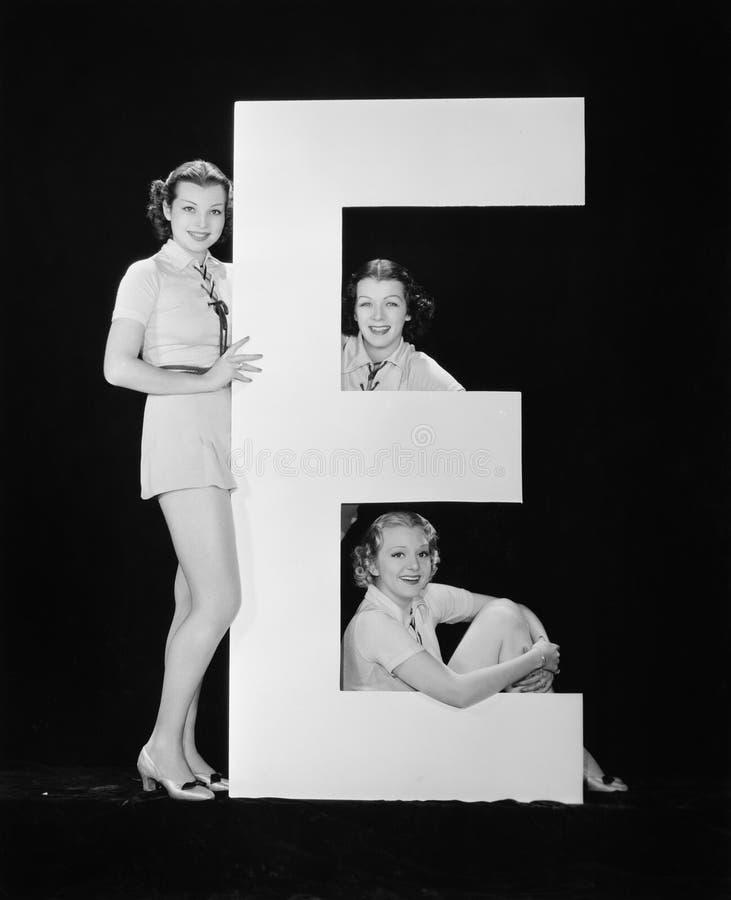 Kvinnor som poserar med enorm bokstav E (alla visade personer inte är längre uppehälle, och inget gods finns Leverantörgarantier  royaltyfri fotografi