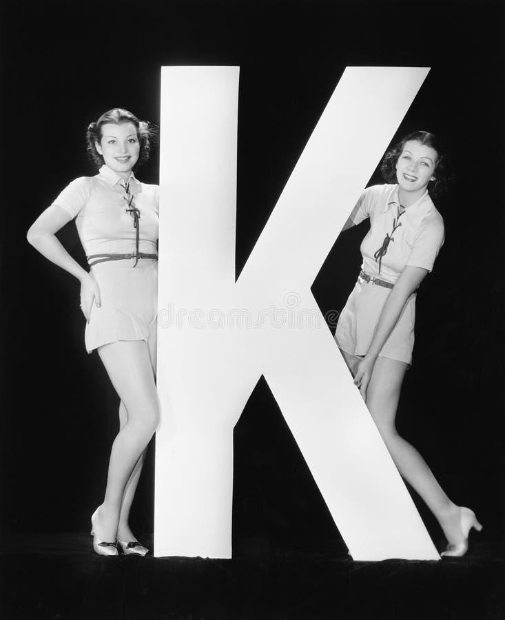 Kvinnor som poserar med enorm bokstav K (alla visade personer inte är längre uppehälle, och inget gods finns Leverantörgarantier  royaltyfri bild