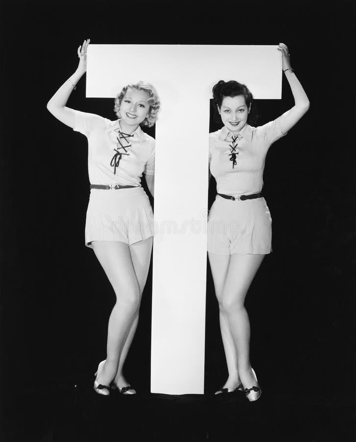 Kvinnor som poserar med enorm bokstav T (alla visade personer inte är längre uppehälle, och inget gods finns Leverantörgarantier  royaltyfria bilder