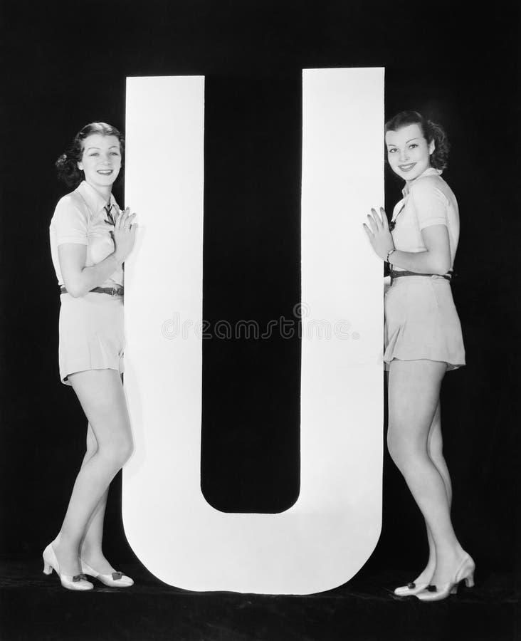 Kvinnor som poserar med enorm bokstav U (alla visade personer inte är längre uppehälle, och inget gods finns Leverantörgarantier  arkivfoto