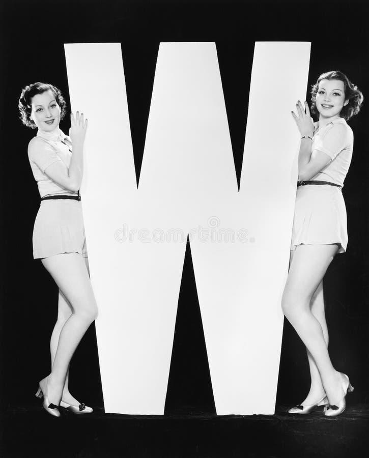 Kvinnor som poserar med enorm bokstav W (alla visade personer inte är längre uppehälle, och inget gods finns Leverantörgarantier  royaltyfri fotografi