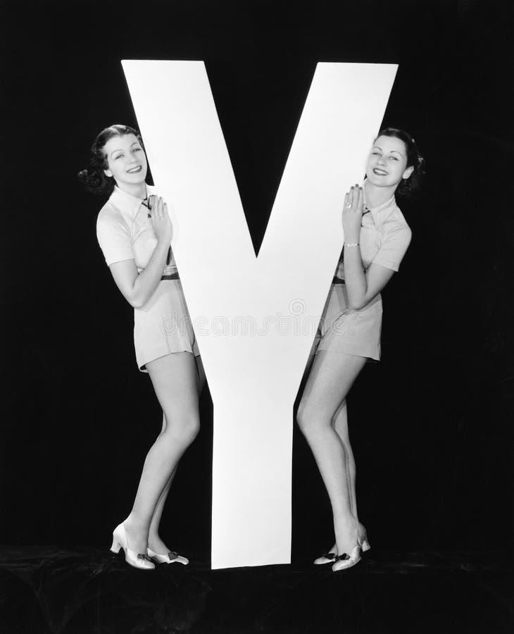 Kvinnor som poserar med enorm bokstav Y (alla visade personer inte är längre uppehälle, och inget gods finns Leverantörgarantier  arkivfoton