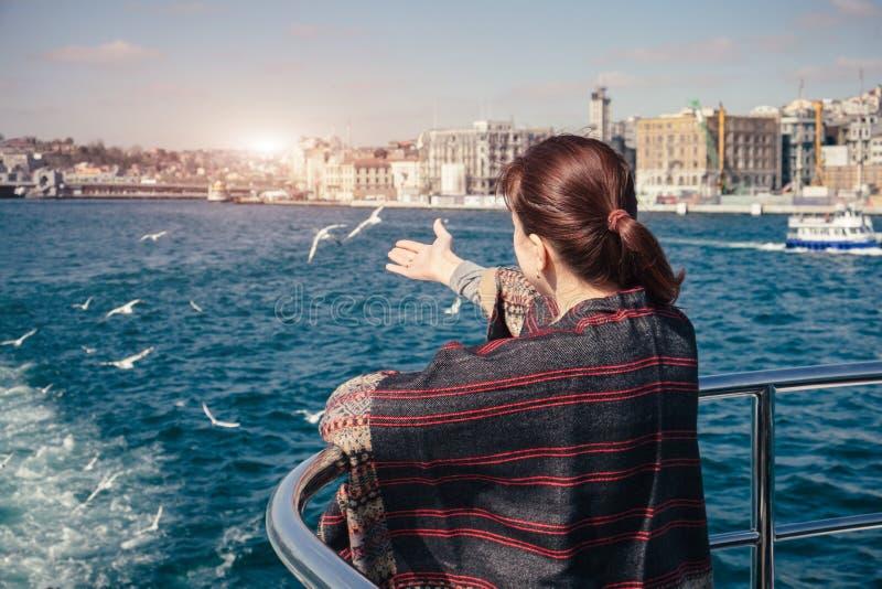 Kvinnor som reser och når seagulls från färjan på Bosphorus royaltyfri bild