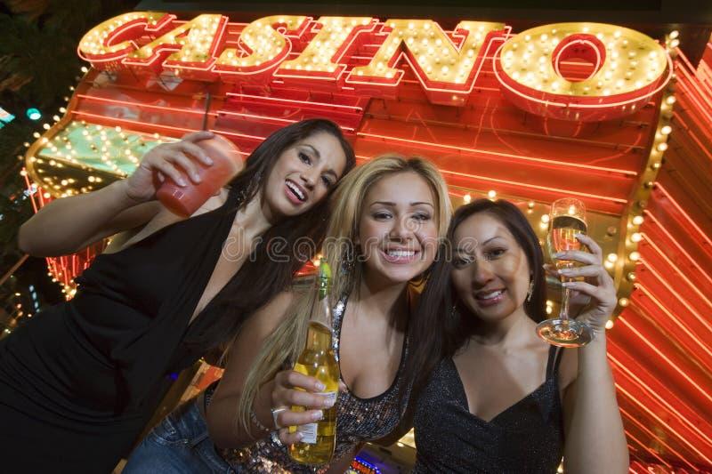 Kvinnor som rymmer Champagne With Casino In The bakgrund fotografering för bildbyråer