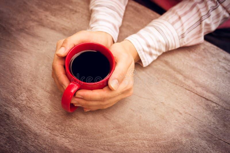 Kvinnor som rymmer den röda kaffekoppen i händer royaltyfri foto