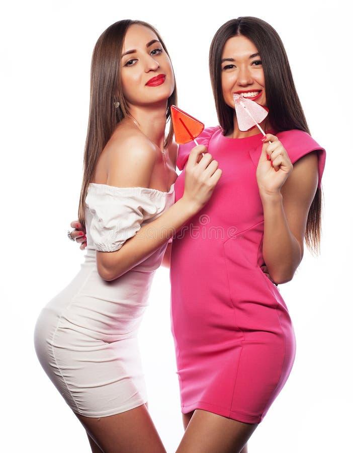Kvinnor som rymmer den rosa lollyen poppar och har gyckel som isoleras tillsammans på vit arkivbilder