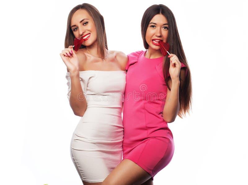 Kvinnor som rymmer den rosa lollyen poppar och har gyckel som isoleras tillsammans på vit royaltyfri fotografi