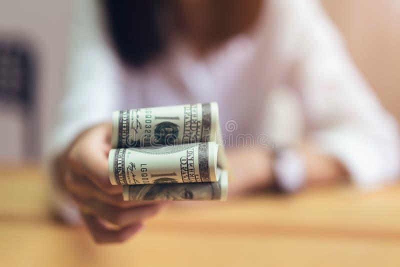 Kvinnor som rymmer och, ger dollarpengar i kontoret Begreppet av utgifter vid kassa fotografering för bildbyråer