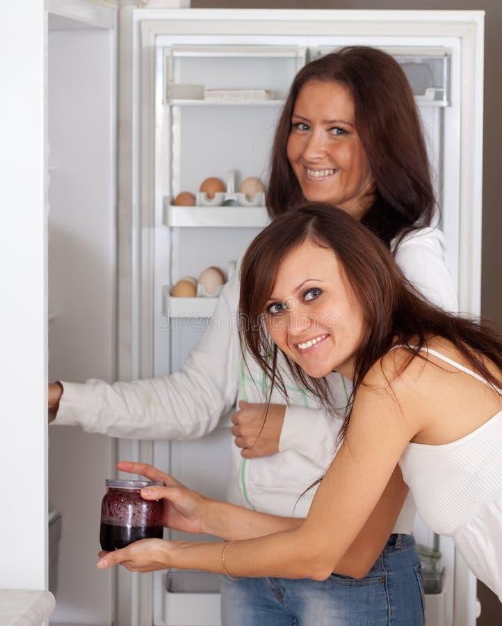 Kvinnor som söker efter något i kylskåp arkivfoto