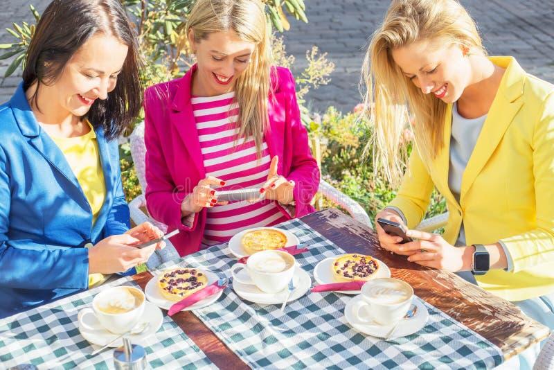 Kvinnor som ser deras smartphones och le arkivbild