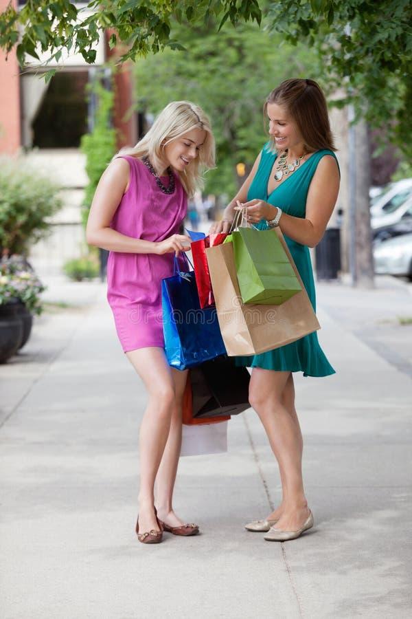 Kvinnor som ser in i shoppingpåsar arkivbilder