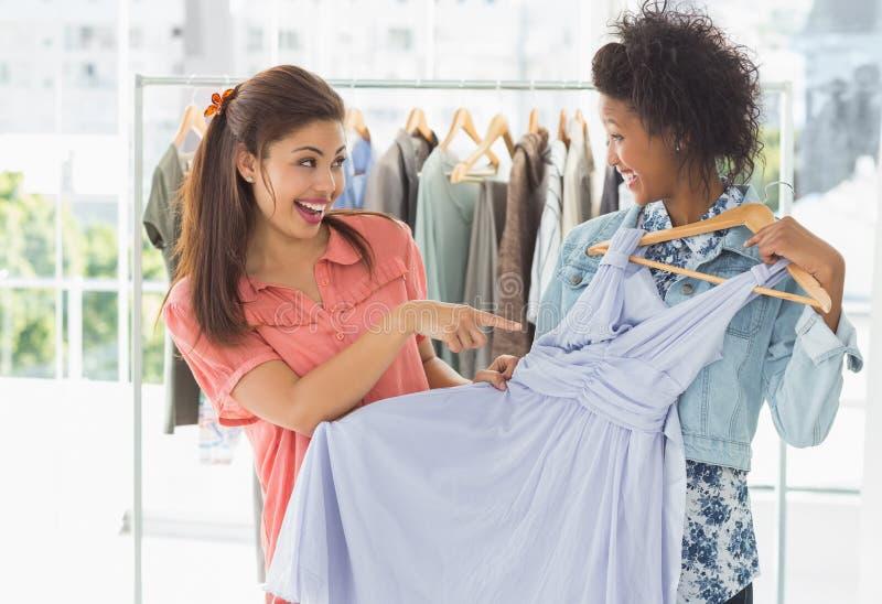 Kvinnor som shoppar i kläderlager royaltyfri fotografi