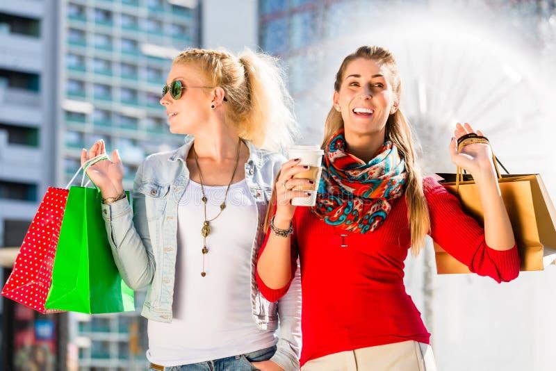 Kvinnor som shoppar i stad med påsar arkivbild