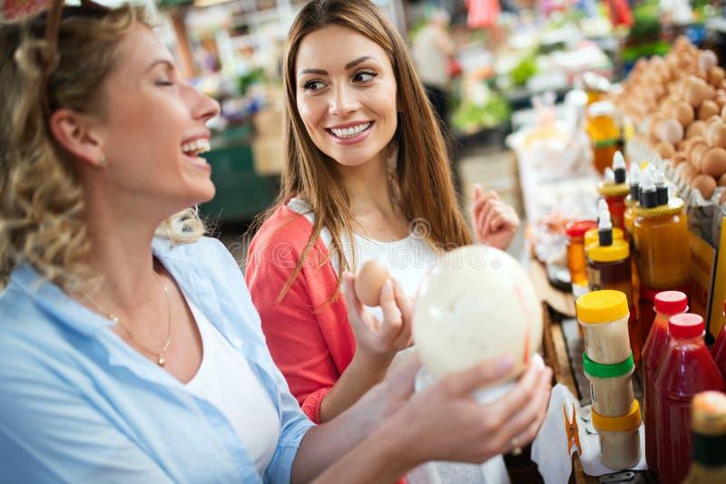 Kvinnor som shoppar nya ägg på den lokala bondemarknaden royaltyfri bild