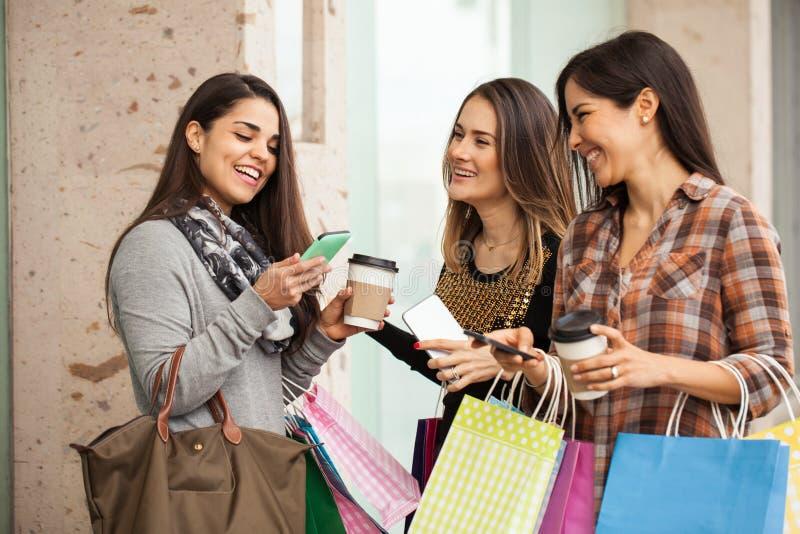 Kvinnor som shoppar och använder deras smartphones royaltyfri fotografi