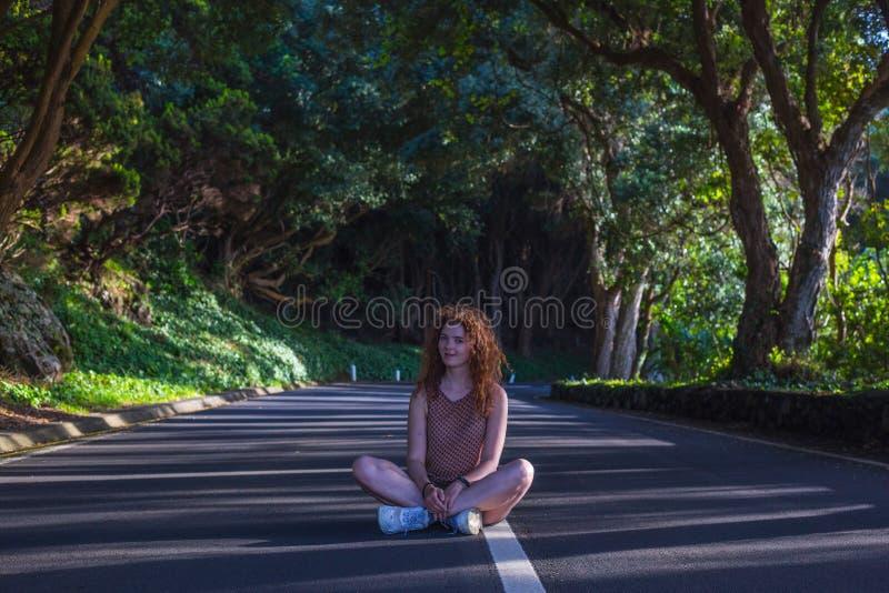 Kvinnor som sitter med korsade ben vid vägen i skogen Terceira, Azorerna Portugal royaltyfria bilder