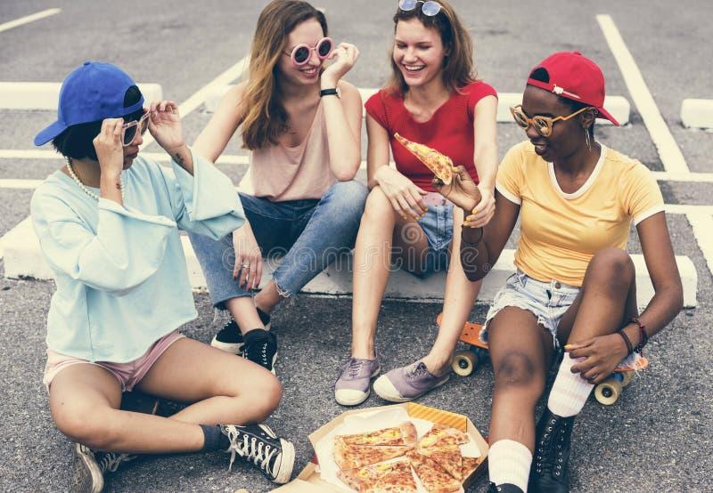 Kvinnor som sitter på golvet och tillsammans äter pizza arkivfoto