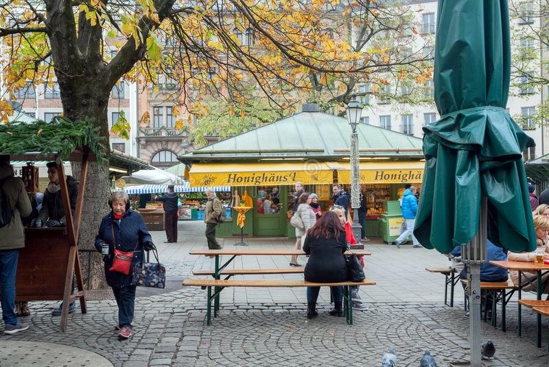 Kvinnor som sitter på tabellen av det utomhus- kafét på berömda Viktualienmarkt fotografering för bildbyråer