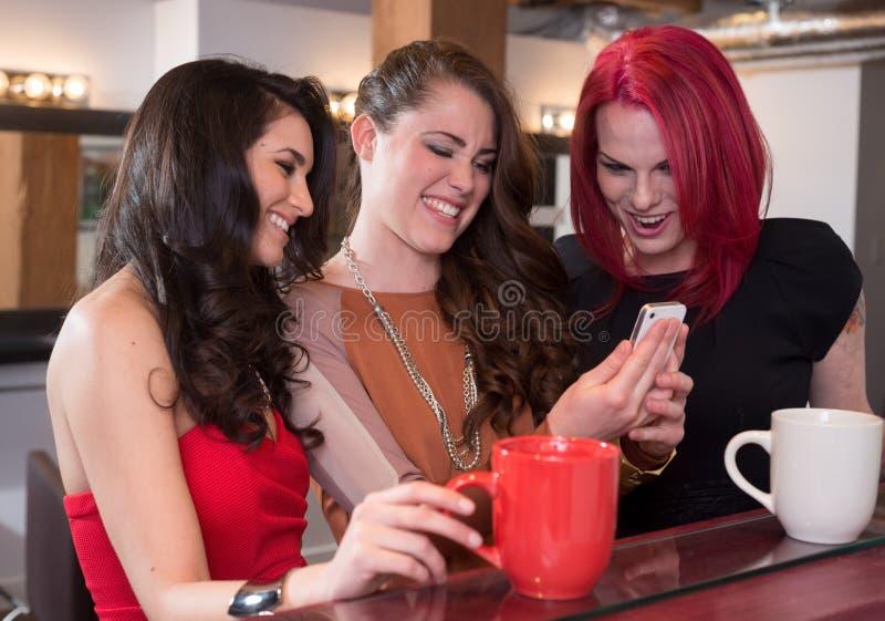 Kvinnor som skrattar med mobiltelefonen royaltyfri foto