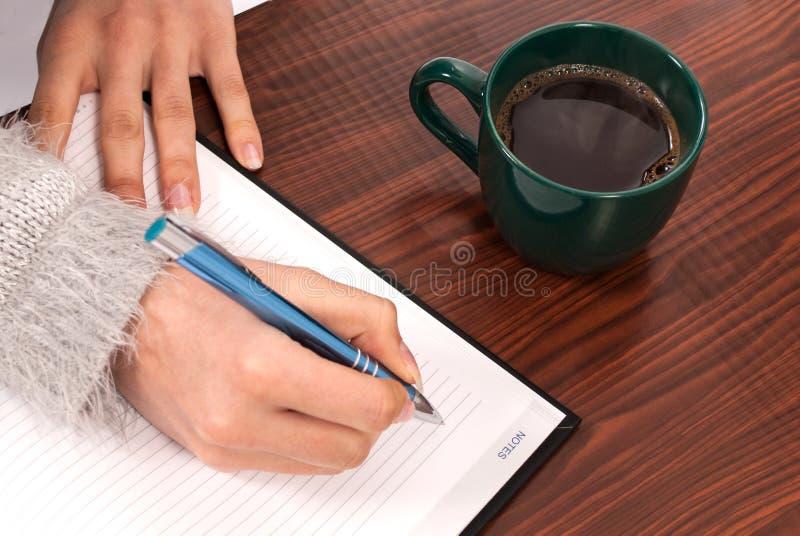 Kvinnor som skriver in i anteckningsboken på träskrivbord- och drinkkaffe royaltyfria bilder