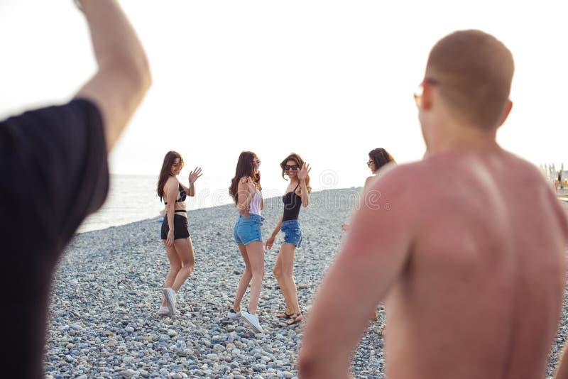Kvinnor som strosar längs kustlinjen kvinnliga vänner som tillsammans går på stranden som tycker om sommarsemester arkivfoto