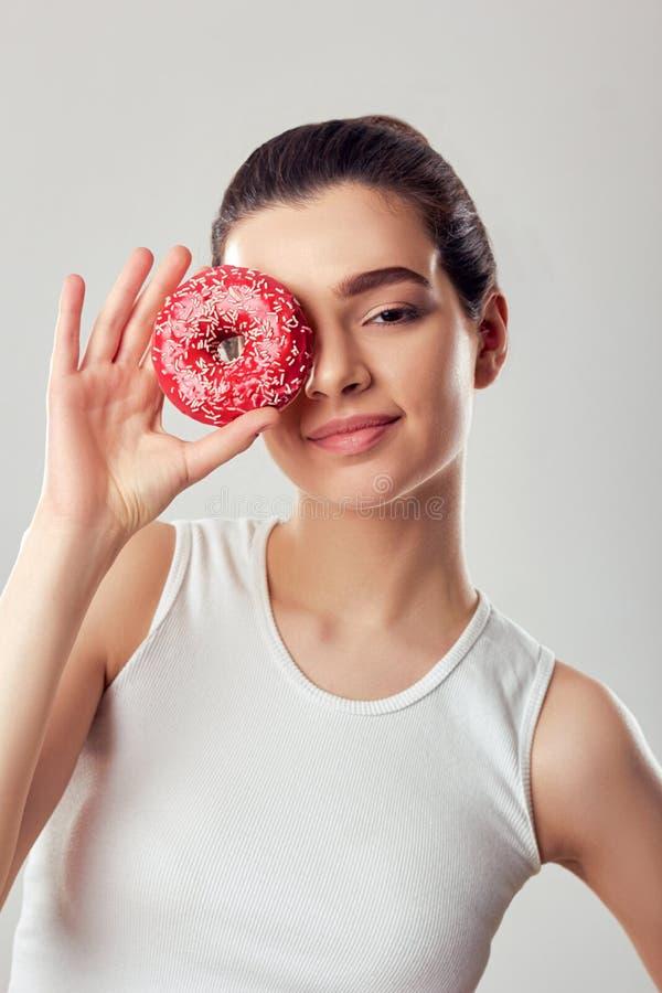 Kvinnor som täcker hennes öga med nöd över den rosa delen Diet Brunette-flickan håller och smakar en rosa öring royaltyfri fotografi
