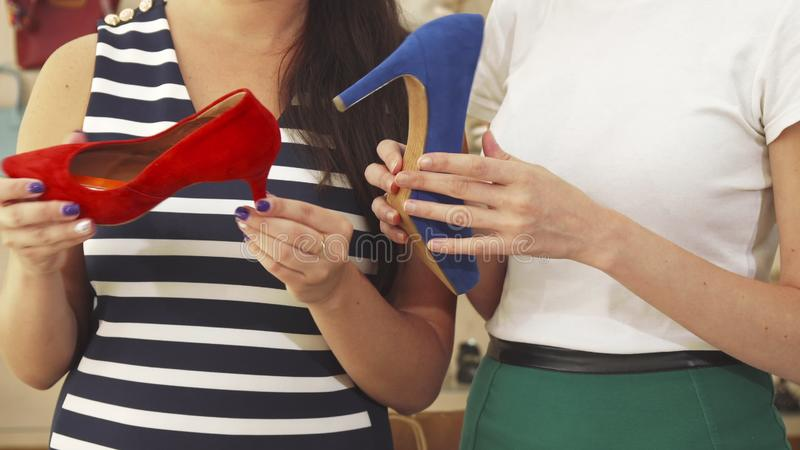 Kvinnor som tätt undersöker olika skor upp royaltyfri foto