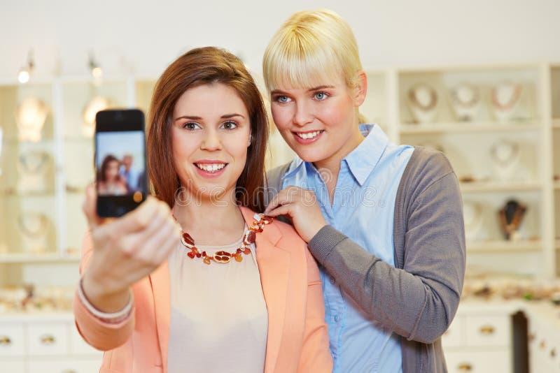 Kvinnor som tar selfie, medan shoppa fotografering för bildbyråer