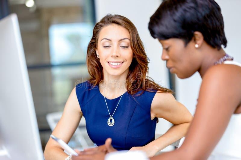 Kvinnor som tillsammans arbetar, kontorsinre arkivfoton