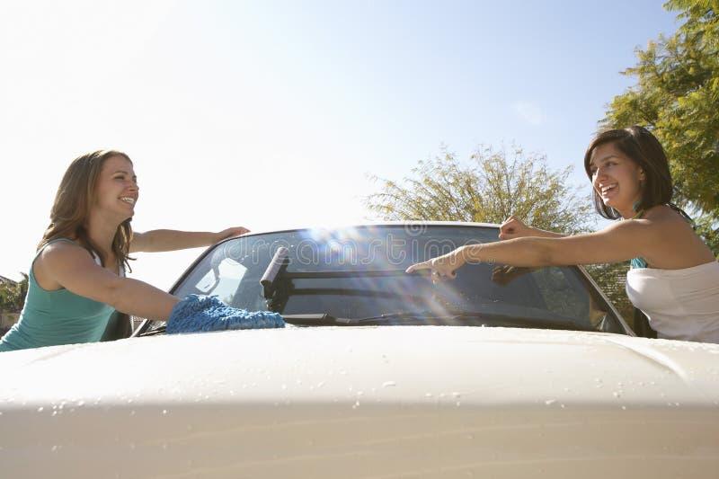 Kvinnor som tillsammans tvättar bilen arkivfoto