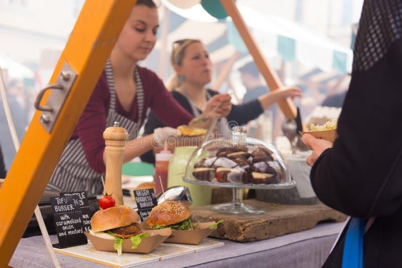 Kvinnor som tjänar som hamburgare på matfestival i Ljubljana, Slovenien royaltyfri fotografi