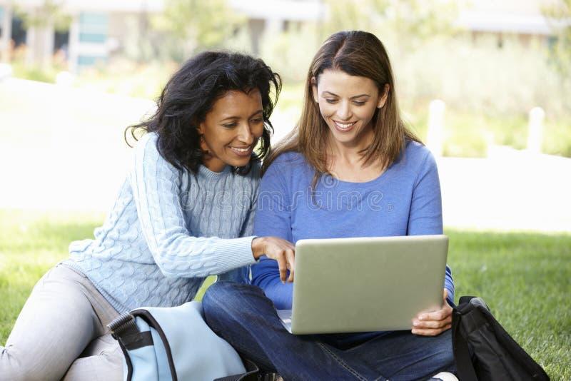 Kvinnor som utomhus använder bärbara datorn royaltyfria foton