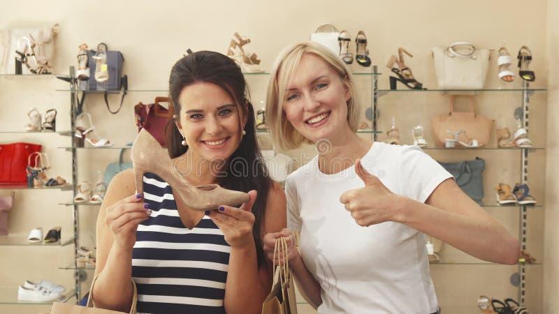 Kvinnor som väljer skor i sko, shoppar arkivfoton