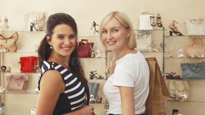 Kvinnor som väljer skor i sko, shoppar arkivbild