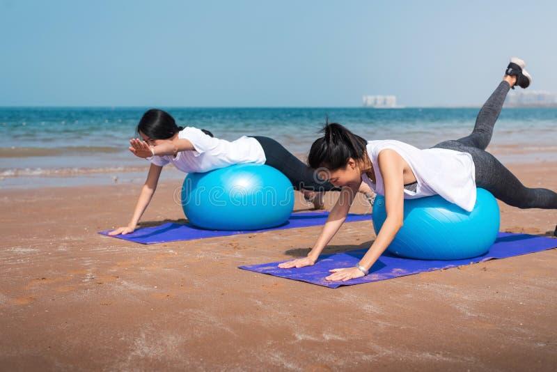 Kvinnor som ?var med pilatesbollen p? stranden royaltyfria bilder