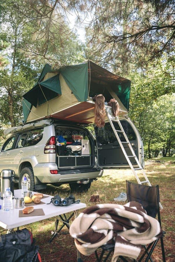 Kvinnor som vilar att ligga i tält över bilen och att se naturen royaltyfri foto