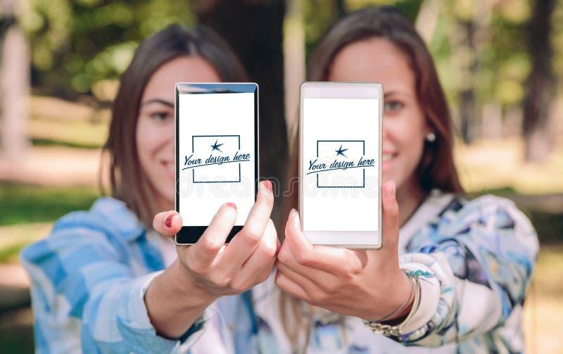 Kvinnor som visar smartphones med deras selfiefoto royaltyfri foto