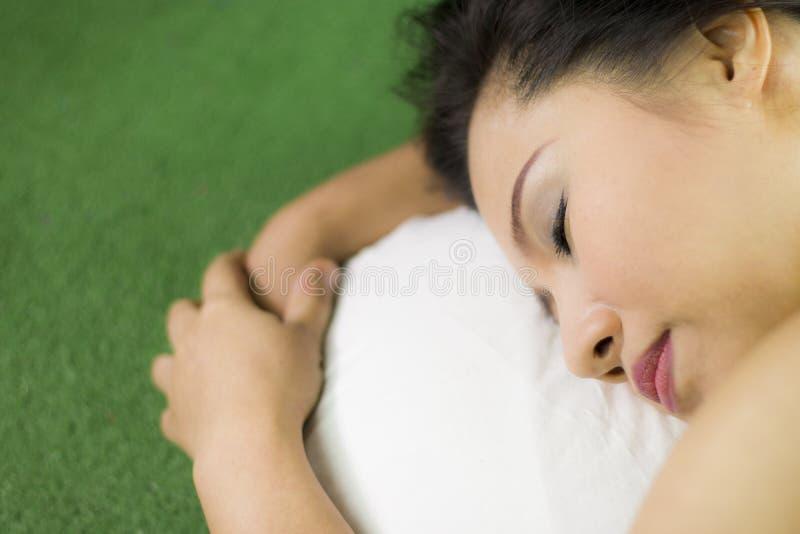 Kvinnor sover på det gröna gräset, en härlig och drömlik thailändsk kvinna som lägger ner på grönt gräs som kopplar av arkivbilder