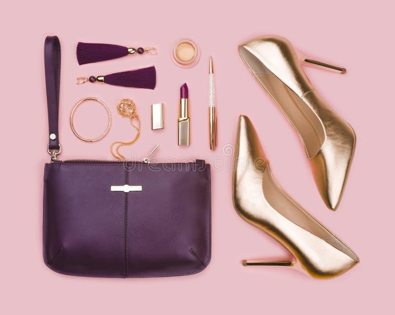 Kvinnor ställde in av guld- purpurfärgad modetillbehör på rosa bakgrund arkivbilder