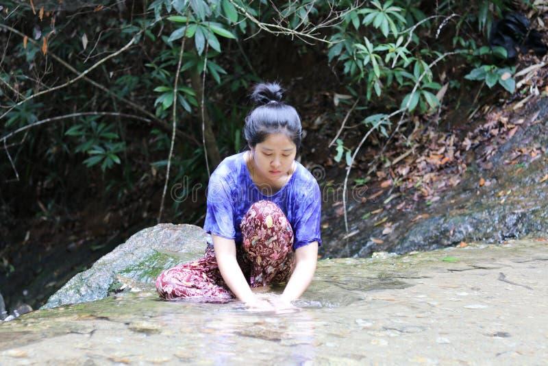 Kvinnor tvättar framsidan bak vattenfallet fotografering för bildbyråer