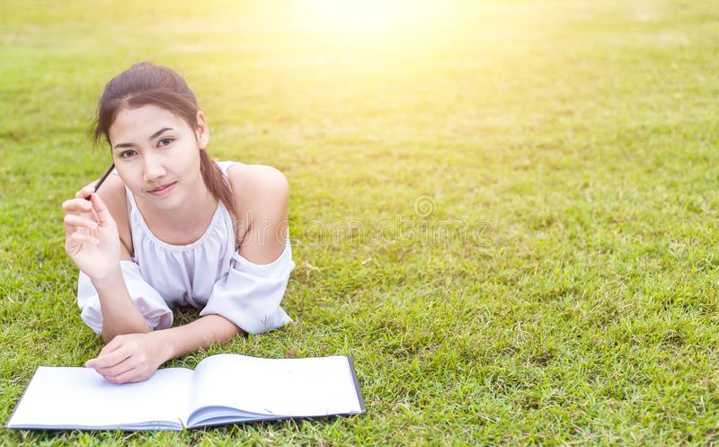 Kvinnorna är på gräset och härligt Hon är tänkande… som dig, är jobbet att finna vad! boken är på gräset hon bär den vita klännin arkivfoton