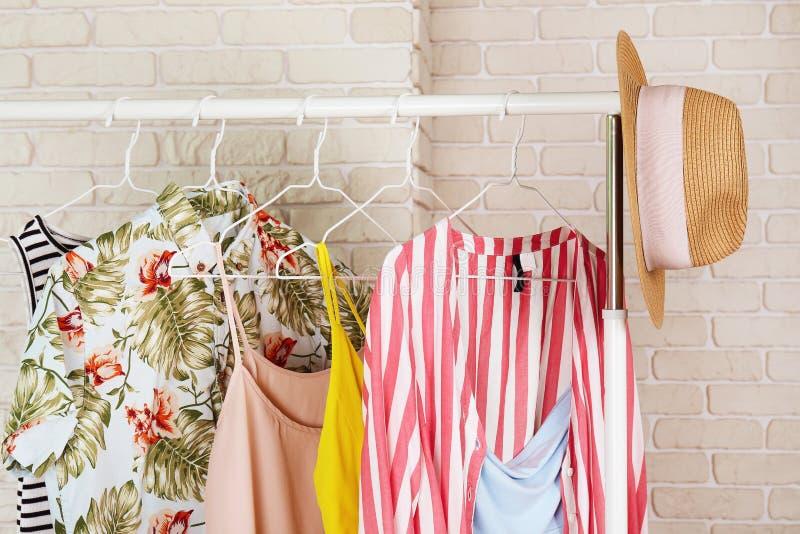 Kvinnors begrepp för lager för höftkläder inre Rad av olik färgrik kvinnlig kläder som hänger på kuggen i hipstermodeshowroo royaltyfria foton